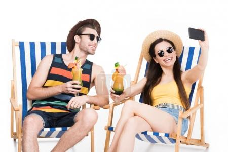 smiling couple resting on beach chairs with cocktails and taking selfie, isolated on white