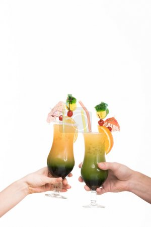 cropped view of couple holding glasses with summer cocktails, isolated on white