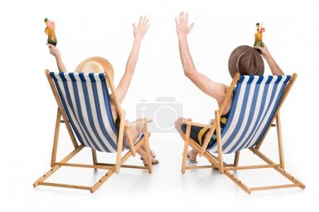 back view of couple relaxing on beach chairs with cocktails, isolated on white