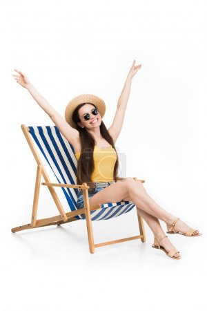 excited beautiful girl resting on beach chair, isolated on white