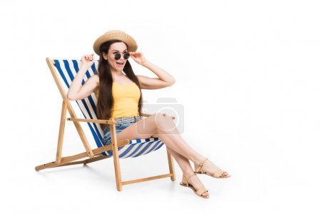 beautiful excited woman relaxing on beach chair, isolated on white