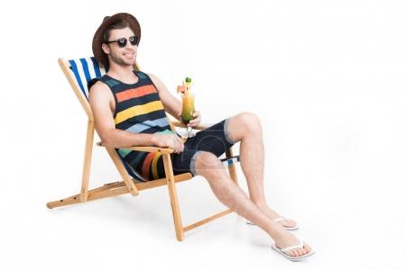 handsome man in sunglasses and hat relaxing on beach chair with cocktail, isolated on white