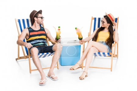 couple relaxing on beach chairs with cocktails and cooler box, isolated on white
