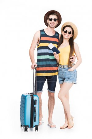 smiling tourists posing with travel bag, isolated on white