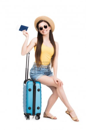 pretty smiling girl with passport, air ticket sitting on travel bag, isolated on white