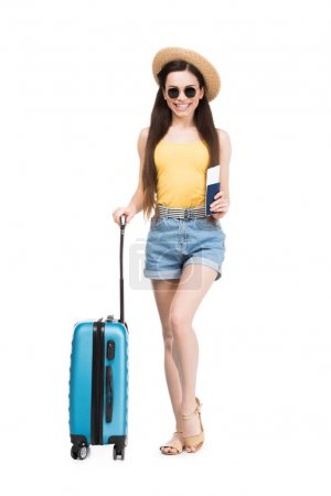 happy female traveler with passport, air ticket and baggage, isolated on white