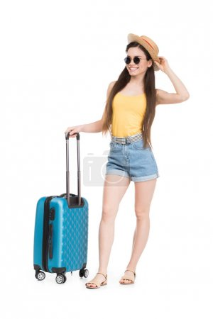 smiling girl in sunglasses and hat posing with luggage for trip, isolated on white