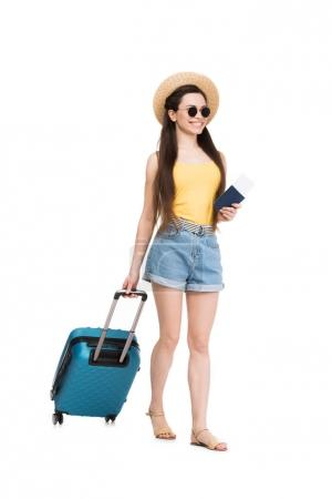smiling female traveler with passport, air ticket and baggage, isolated on white