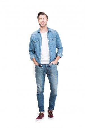 Photo pour Jeune homme souriant en jeans regardant la caméra, isolé sur blanc - image libre de droit