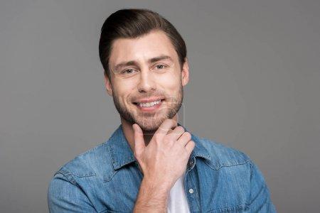 Portrait de bel homme souriant, isolé sur fond gris