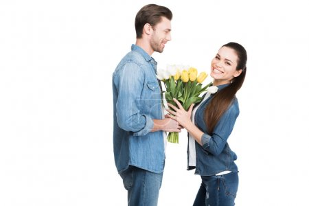 happy couple with bouquet of spring tulips for international womens day, isolated on white