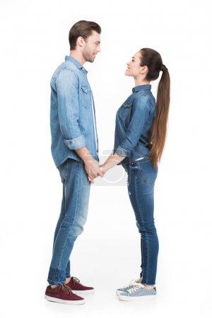 Photo pour Jeune couple tenant la main et se regardant, isolé sur blanc - image libre de droit