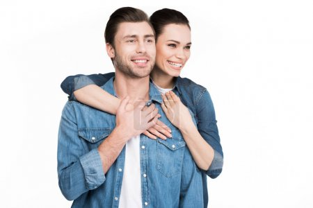 Photo for Young smiling couple in denim clothes hugging isolated on white - Royalty Free Image