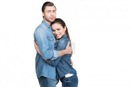 cheerful young couple embracing and looking at camera, isolated on white