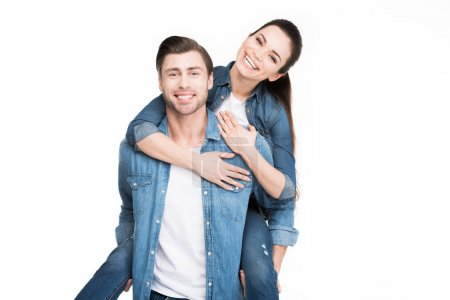 Photo for Young smiling man piggybacking cheerful girlfriend, isolated on white - Royalty Free Image