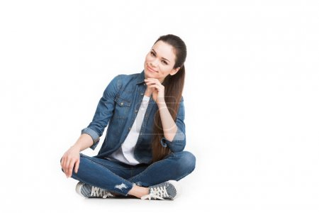 beautiful brunette woman sitting in jeans clothes, isolated on white