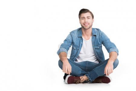 young smiling man sitting in jeans looking at camera, isolated on white