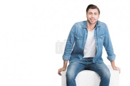 handsome smiling man sitting on white cube, isolated on white