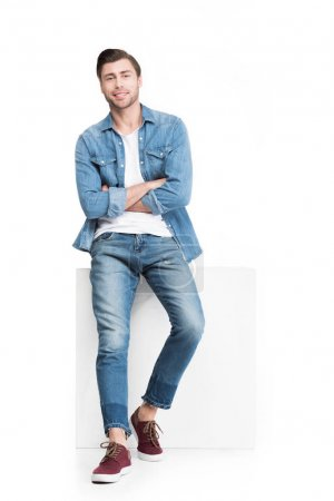 young smiling man in denim leaning on white cube, isolated on white