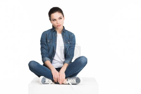 young pretty woman in jeans sitting on white cube, isolated on white