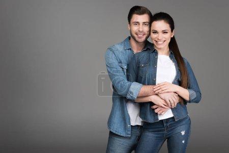 happy couple hugging isolated on grey