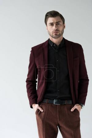 handsome serious man posing in fashionable jacket, isolated on grey