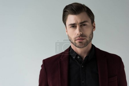 portrait of handsome stylish man posing in jacket, isolated on grey