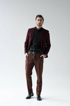 Foto de Hombre guapo elegante posando en traje de moda, aislado en gris - Imagen libre de derechos