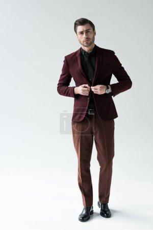 Photo pour La mode homme posant en costume tendance, isolé sur fond gris - image libre de droit