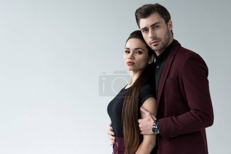 handsome man hugging sensual woman, isolated on grey