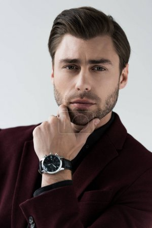 Photo for Pensive stylish man posing with wristwatch, isolated on grey - Royalty Free Image