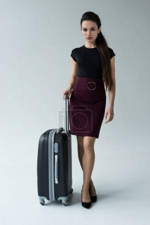 confident woman posing with travel bag, isolated on grey