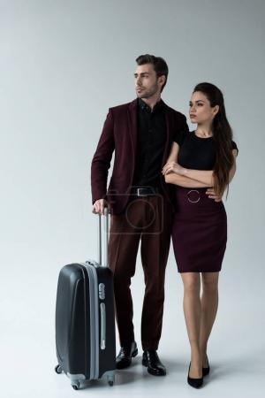 serious couple with luggage ready for trip, isolated on grey