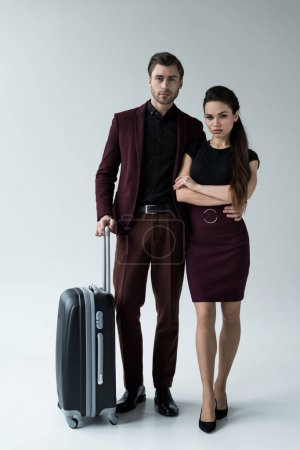 serious couple with travel bag ready for trip, isolated on grey