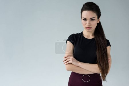 confident woman with crossed arms looking at camera, isolated on grey
