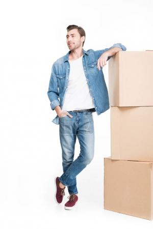 happy young man moving with cardboard boxes, isolated on white