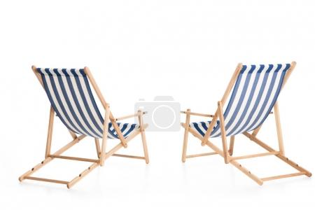 rear view of two beach chairs, isolated on white