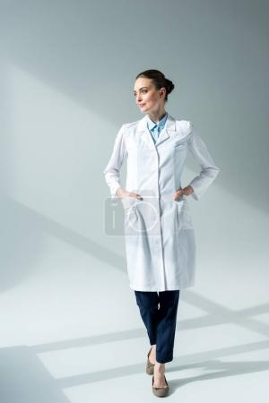 serious female doctor in white coat looking away on grey