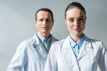 Photo for Close-up portrait of attractive adult doctors looking at camera on grey - Royalty Free Image