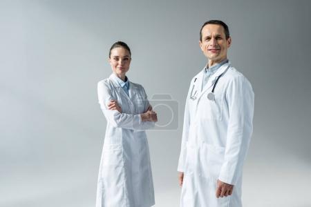 Photo pour Médecins adultes souriants regardant la caméra isolée sur gris - image libre de droit