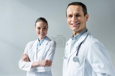 happy adult doctors looking at camera isolated on grey