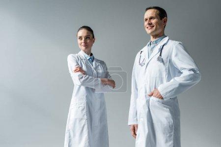 heureux médecins adultes à la recherche de suite sur fond gris
