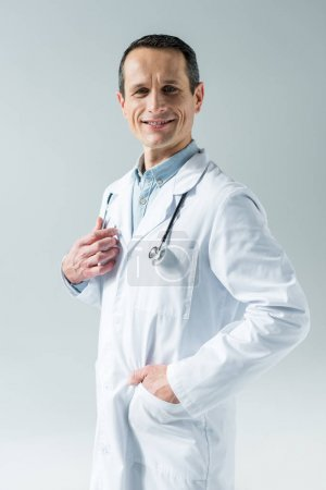 handsome adult doctor with stethoscope looking at camera isolated on grey