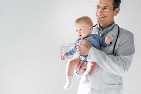 handsome adult pediatrician holding little baby isolated on grey