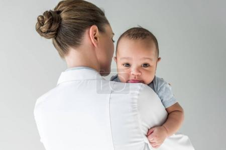 rear view of female pediatrician with african american baby isolated on grey