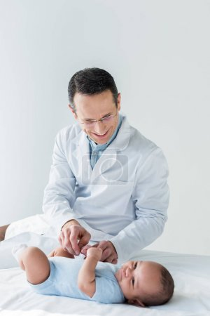 handsome adult pediatrician playing with little baby while sitting on bed