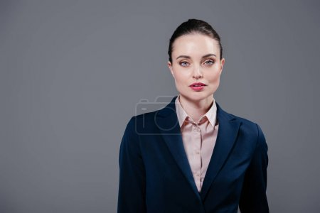 serious adult businesswoman looking at camera isolated on grey