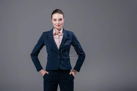 Photo for Smiling adult businesswoman with hands in pockets looking at camera isolated on grey - Royalty Free Image