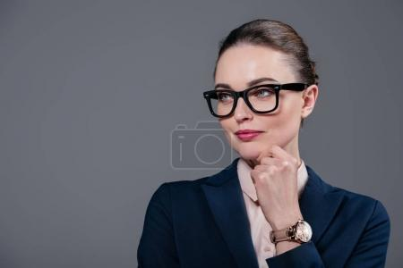 close-up portrait of adult businesswoman in stylish vintage eyeglasses isolated on grey