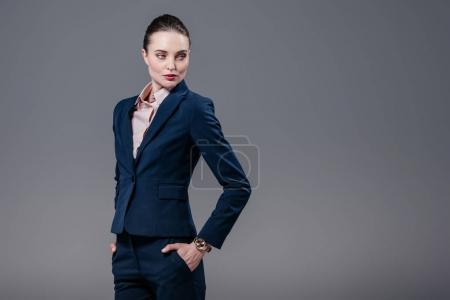 attractive adult businesswoman with hands in pockets looking away isolated on grey